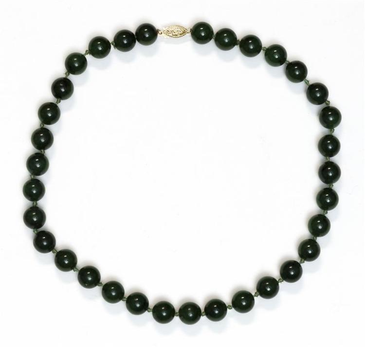 SPINACH-GREEN JADE NECKLACE Thirty-three 10 mm beads strung on silk. 14k gold clasp. Length 15
