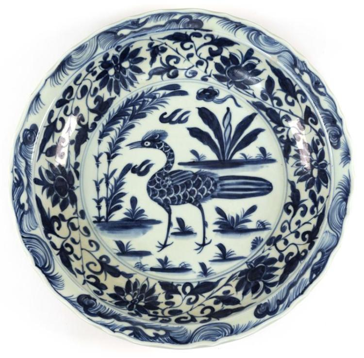 BLUE AND WHITE PORCELAIN DISH Central bird in a landscape surrounded by lotus flowers and feather decoration along a scalloped edge....