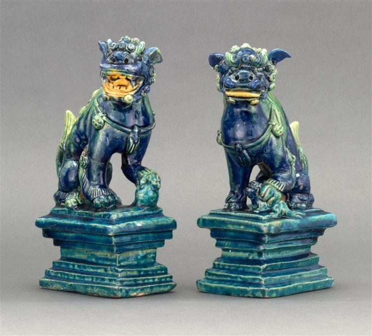 PAIR OF BLUE AND GREEN GLAZE STONEWARE FIGURES In the form of guardian lions seated on rectangular plinths. One holding a pup and th...