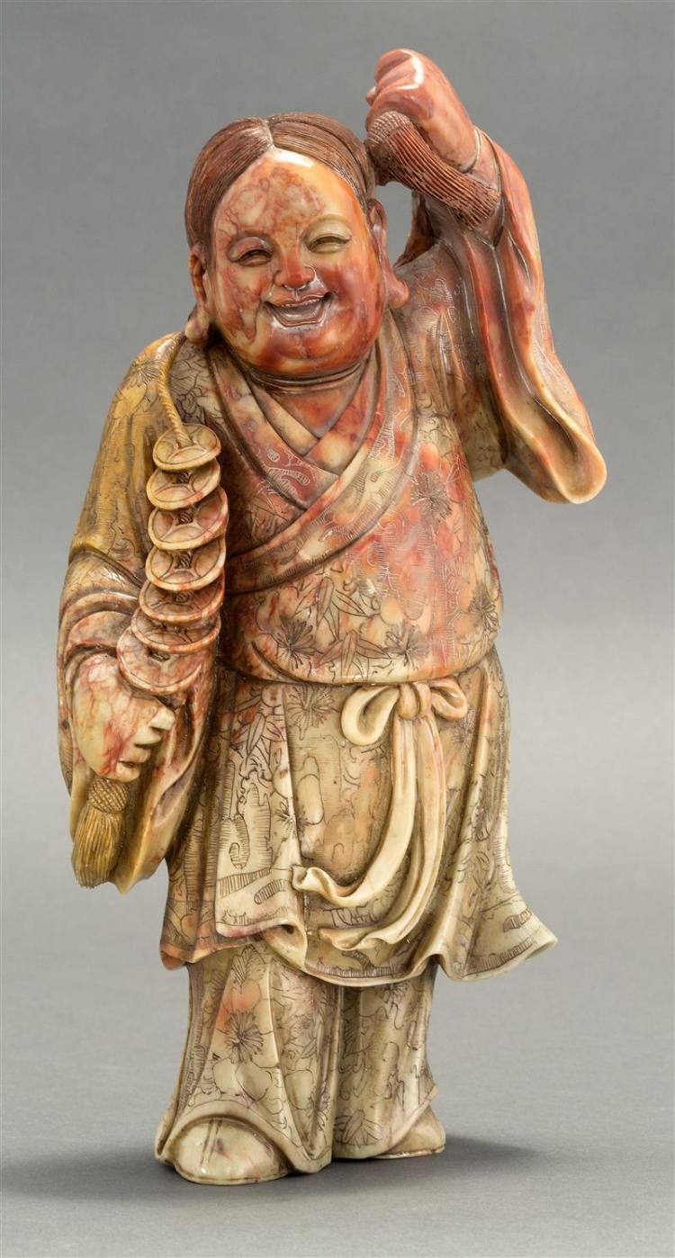 RED AND BEIGE SOAPSTONE CARVING In the form of Liu Hai holding a string of cash. Height 11.25