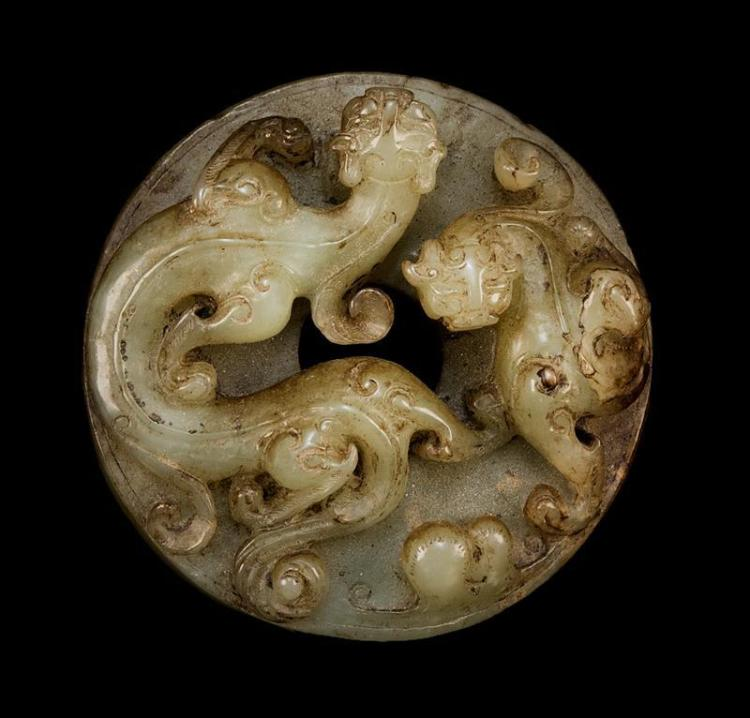 CELADON AND BROWN JADE BI With high-relief carving of qilong dragons on one face; rice design on reverse. Diameter 2.4