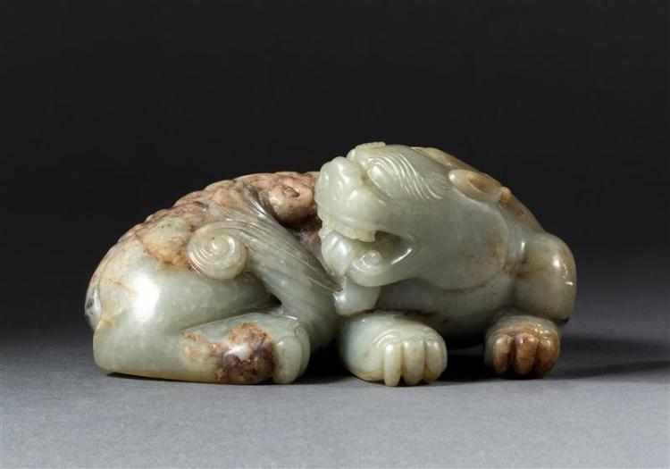 CELADON AND RUSSET JADE CARVING In the form of a reclining qilin with forked tail and single horn. Length 5.5