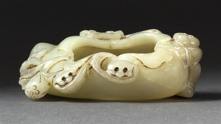 CELADON JADE WRITER''S COUPE In the form of a folded lotus leaf with relief-carved figure, ruyi, and lotus pods. Length 3.75