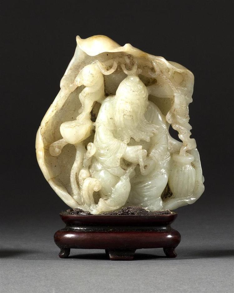 CELADON AND RUSSET JADE CARVING In the form of a seated lohan inside a lotus leaf. With monkey and carp. Height 3.3