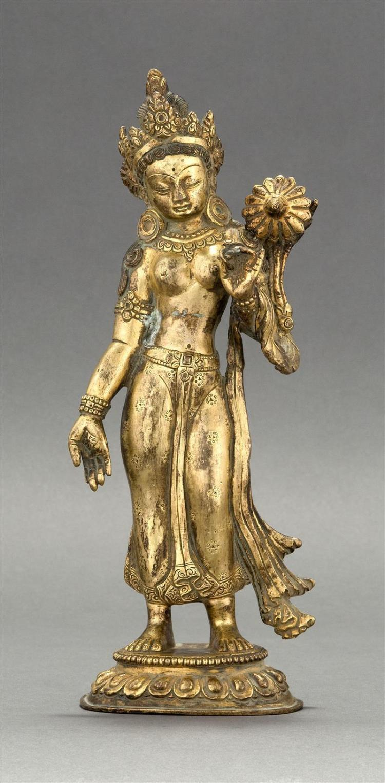 SINO-TIBETAN GILT-BRONZE FIGURE OF TARA In standing position on an oval lotus base. Height 10.75