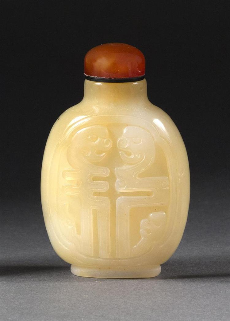 CHALCEDONY AGATE SNUFF BOTTLE In elongated ovoid form with stylized calligraphy design featuring dragons'' heads. Height 2.4