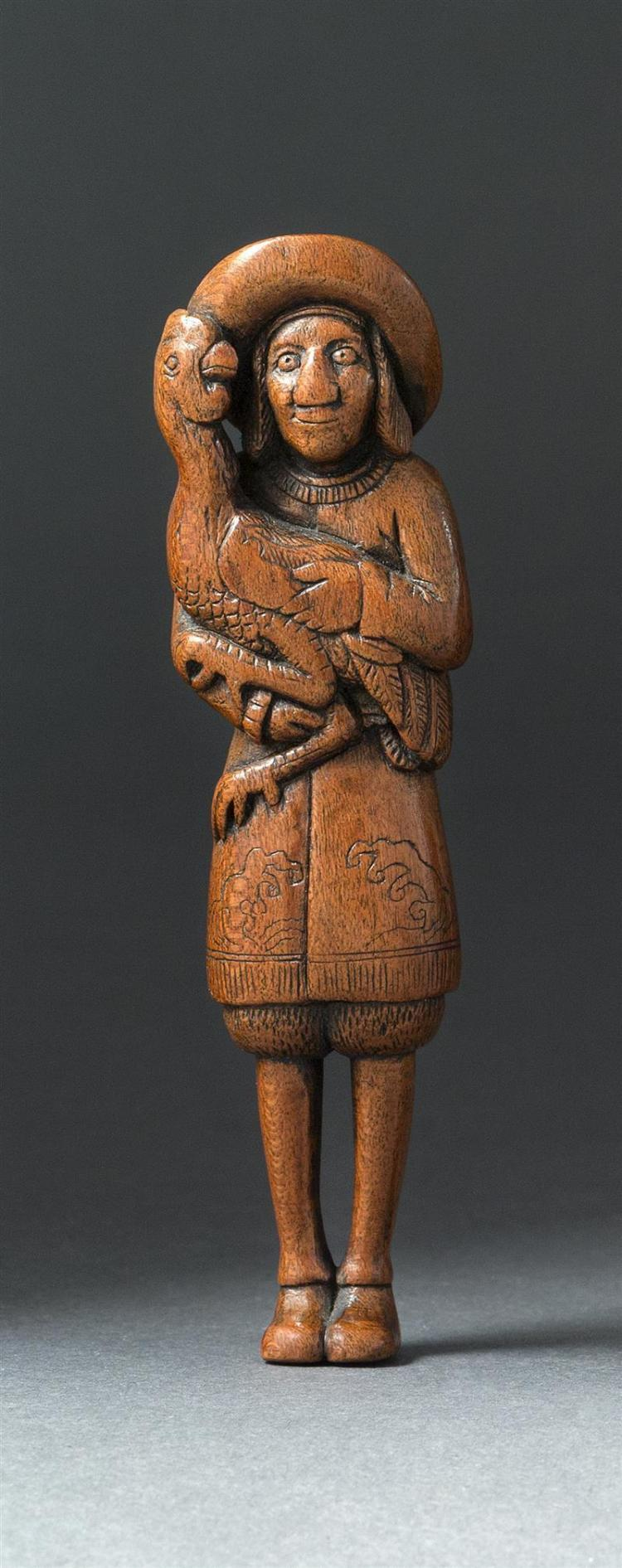 WOOD NETSUKE In the form of a Dutchman with wave-decorated costume standing while holding a rooster. Height 4.25