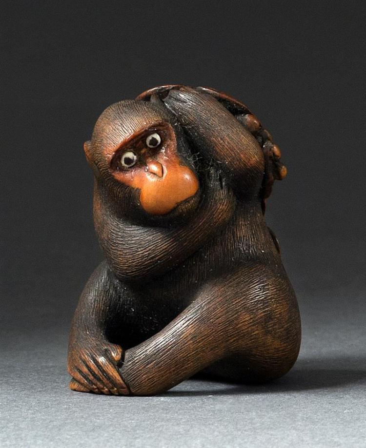 WOOD NETSUKE In the form of a seated monkey with inlaid eyes holding grapes and a grapevine. Signed