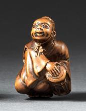 WOOD NETSUKE By Minkoku. Depicting a kneeling man beating a drum. Signed. Height 1.3