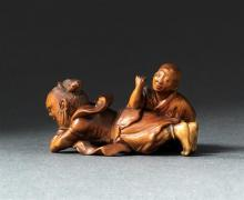 WOOD NETSUKE By Minkoku. In the form of a nio receiving a massage from a blind man. Signed. Length 1.6