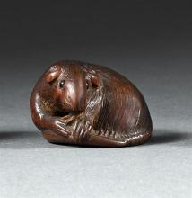 WOOD NETSUKE By Toyomasa. In the form of a reclining rat with inlaid eyes holding a radish. Signed. Length 1.5