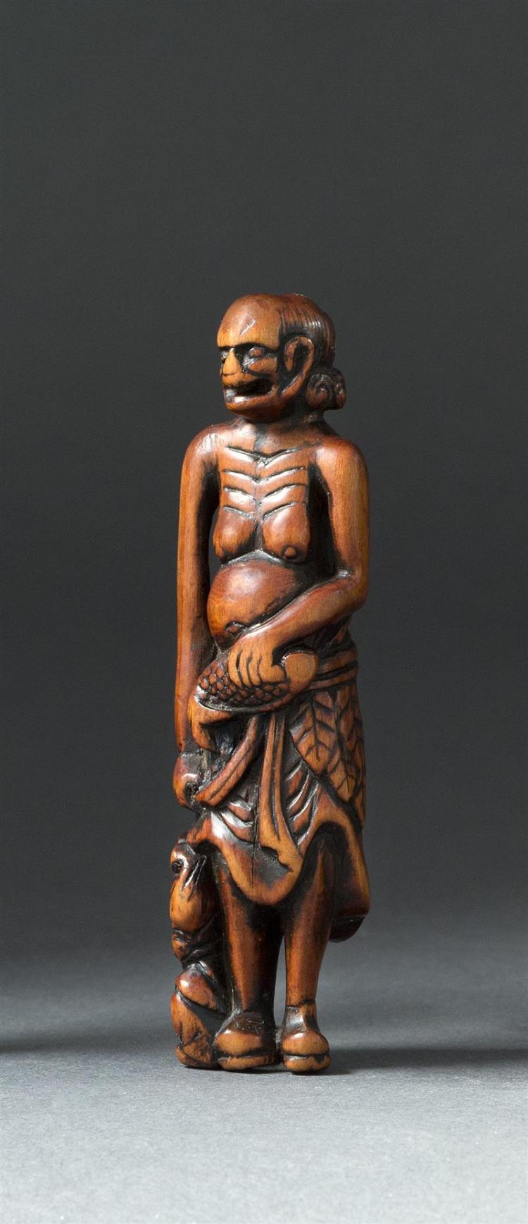 WOOD NETSUKE In the form of an emaciated sennin wearing a mugwart skirt and holding a fish while attended by a small figure at his f...