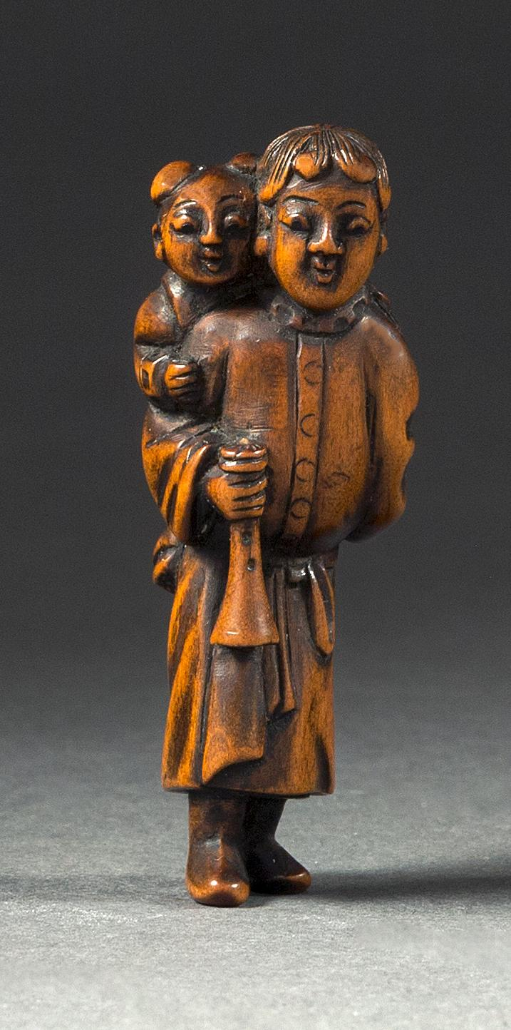 WOOD NETSUKE In the form of a young man carrying a youth on his back while holding a trumpet. Height 2.1