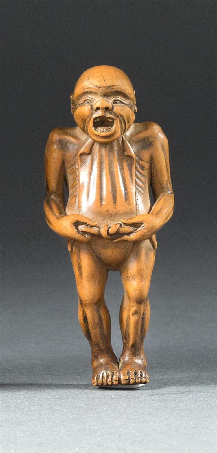 WOOD NETSUKE In the form of a peasant standing while tying his loincloth. Height 2.6