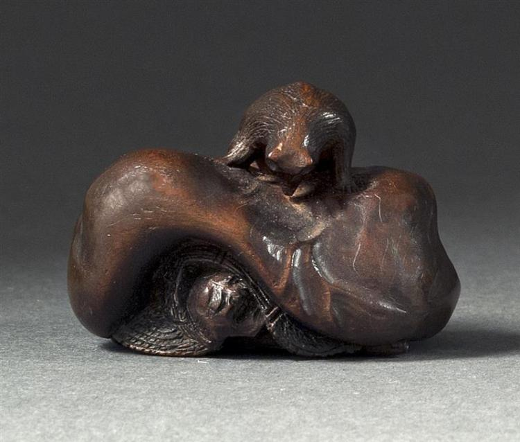 WOOD NETSUKE By Kunihiro. In the form of a badger trapping a hunter. Signed. Length 1.5