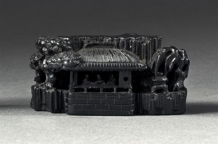EBONY NETSUKE By Masatoshi. In the form of a pavilion with figures in a forested landscape. Signed. Length 2