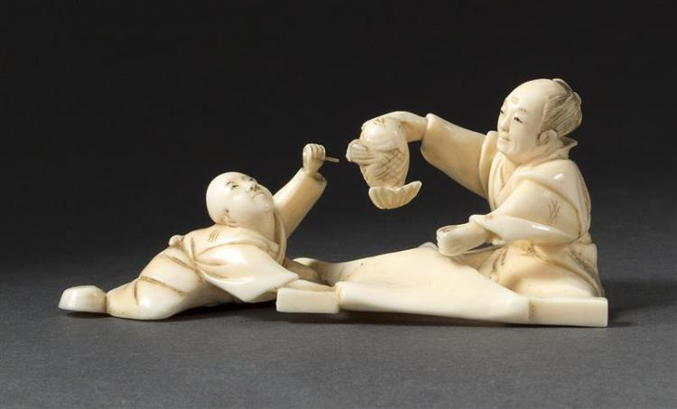 IVORY OKIMONO In the form of a fisherman and child with a fish. Length 3.4