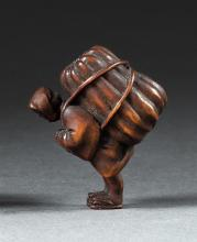 WOOD NETSUKE In the form of a farmer carrying a large melon on his back. Height 1.5