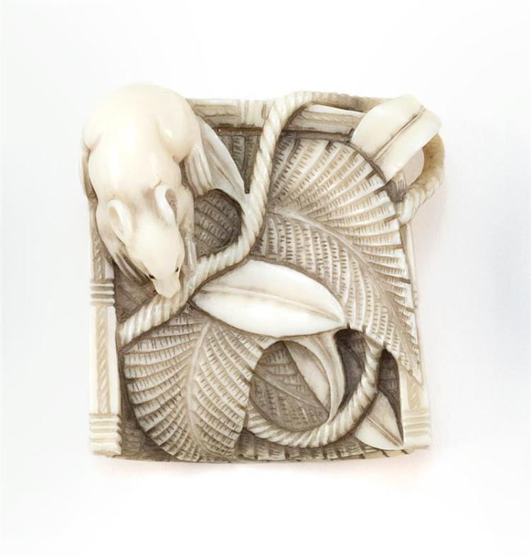 IVORY NETSUKE In the form of a rat on a winnowing basket. Signed