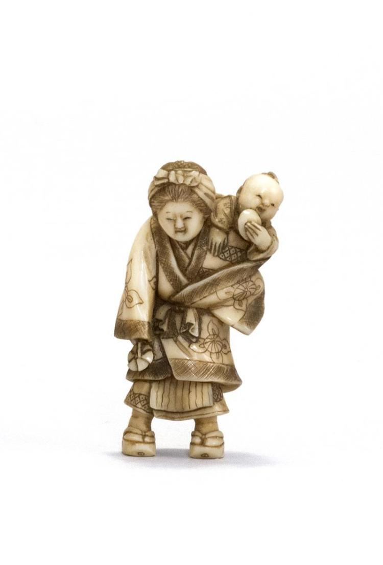 IVORY NETSUKE Depicting a woman carrying a child. Signed