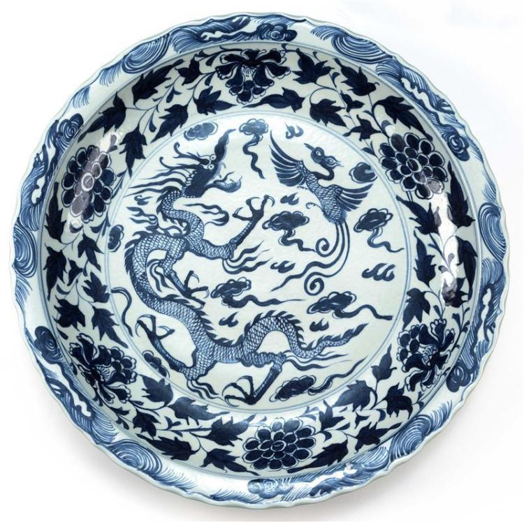 LARGE BLUE AND WHITE PORCELAIN CHARGER With central decoration of a three-claw dragon and phoenix among clouds and flaming pearls, s...