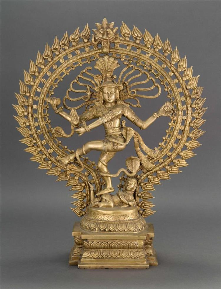 INDIAN BRONZE FIGURE Depicting four-armed Shiva dancing on a demon figure with a flaming mandala at his back. Height 27.25