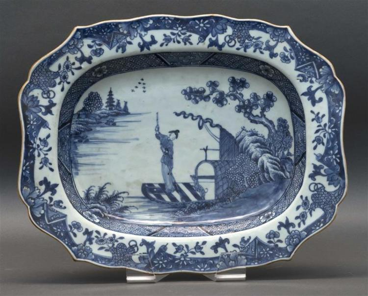 BLUE AND WHITE PORCELAIN PLATTER Boatman with a dog in a river landscape, surrounded by a floral and landscape border. Shaped edge w...