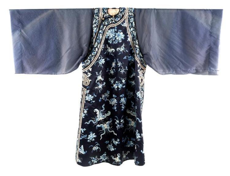 BLUE SILK EMBROIDERED ROBE With needlework bats, peonies, fruit, and plum blossom design on a dark blue ground. Descended in the fam...
