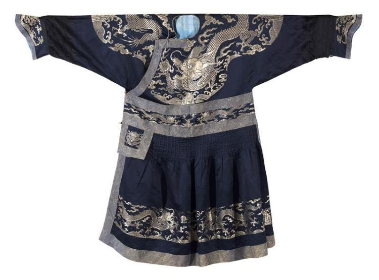 BLUE SILK DRAGON ROBE With counted stitch four-claw dragon design on a blue ground. Gilt-bronze buttons, numerous dragons, and pleat...