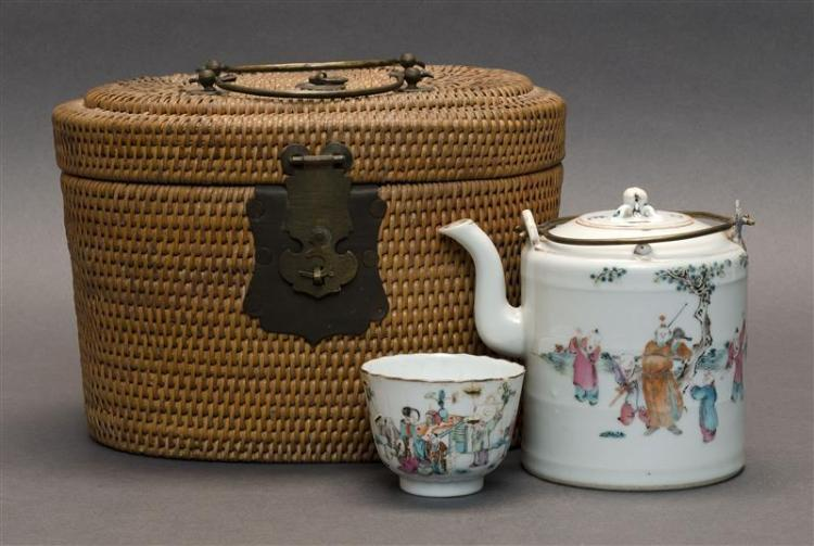 POLYCHROME PORCELAIN TEAPOT WITH MATCHING CUP In a wicker caddy with figural landscape design. Height of teapot 4.5