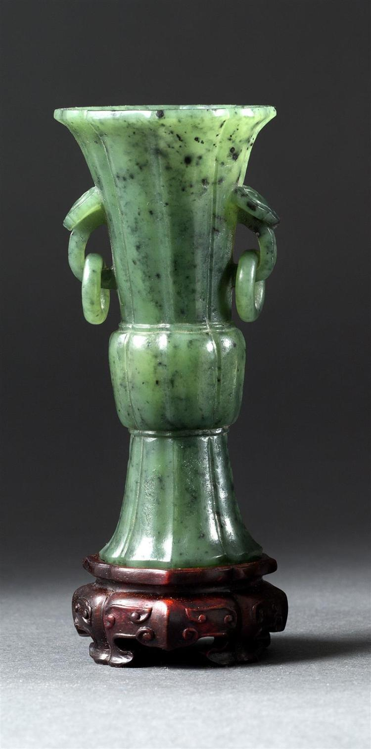 SPINACH-GREEN JADE VASE In trumpet form with ruyi and loose ring handles. Height 3.8