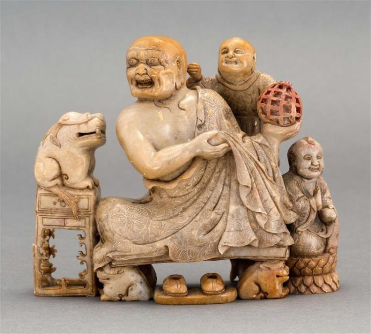 THREE-COLOR SOAPSTONE CARVING Depicting a seated lohan with two youthful attendants and guardian lions. Length 6