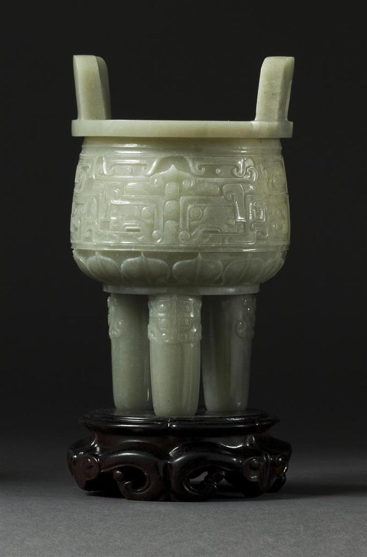 CELADON JADE CENSER In ovoid form with tripod base and loop handles. Body and legs carved with stylized mask designs. Height 5.5