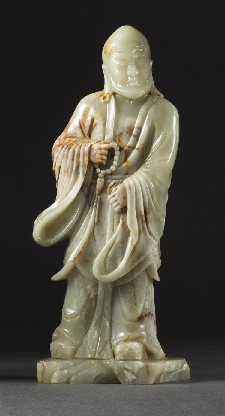 GRAY AND RUSSET JADE CARVING In the form of a standing lohan holding prayer beads. Height 9.5