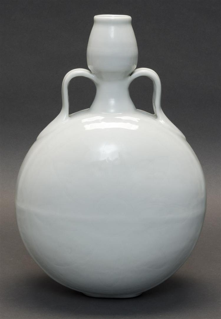 BLANC DE CHINE PORCELAIN HANDLED VASE In pilgrim flask form. With tulip-form mouth and faintly incised central floral decoration on...