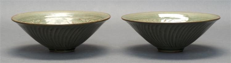 TWO LONGQUAN DARK CELADON PORCELAIN BOWLS Both in conical form. With crazed glaze and incised floral , fish, and bird design. Height...