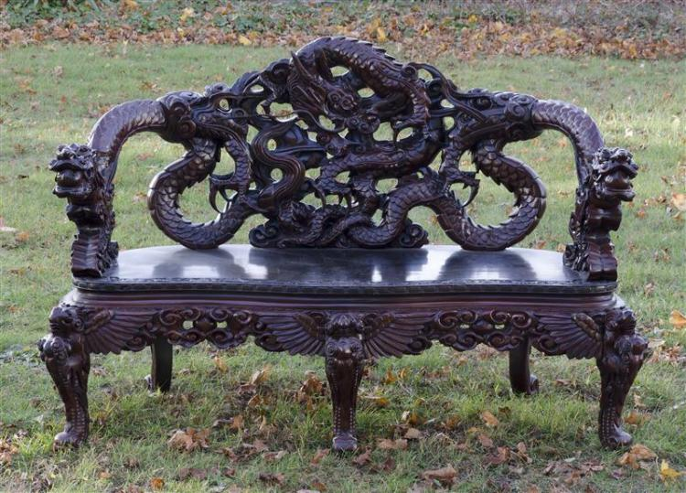 ORNATE DRAGON-CARVED SETTEE In a stained fruitwood, with dragon-form arms, back, and knees. Height 37