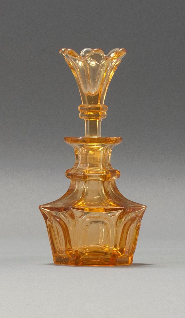 SANDWICH GLASS COMPANY BLOWN-MOLDED OVAL PANELLED FRAMES COLOGNE BOTTLE WITH LILY STOPPER In brilliant amber. Retains original stopp...
