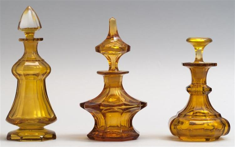 "THREE CUT GLASS COLOGNE BOTTLES All in amber. Heights from 5"" to 6.75"". From a Cape Cod Collection of Early Glass."