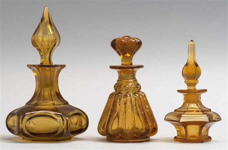"THREE BLOWN-MOLDED GLASS COLOGNE BOTTLES All in amber. Heights from 3.75"" to 6"". From a Cape Cod Collection of Early Glass."