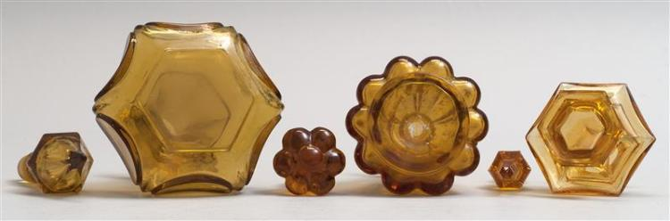 THREE BLOWN-MOLDED GLASS COLOGNE BOTTLES All in amber. Heights from 3.75