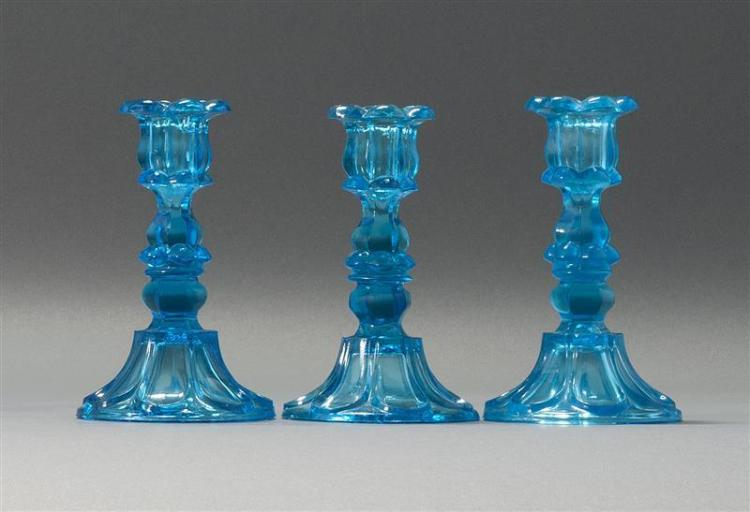 THREE SANDWICH GLASS COMPANY PRESSED GLASS CANDLESTICKS In Loop and Petal pattern in electric blue. Heights 7