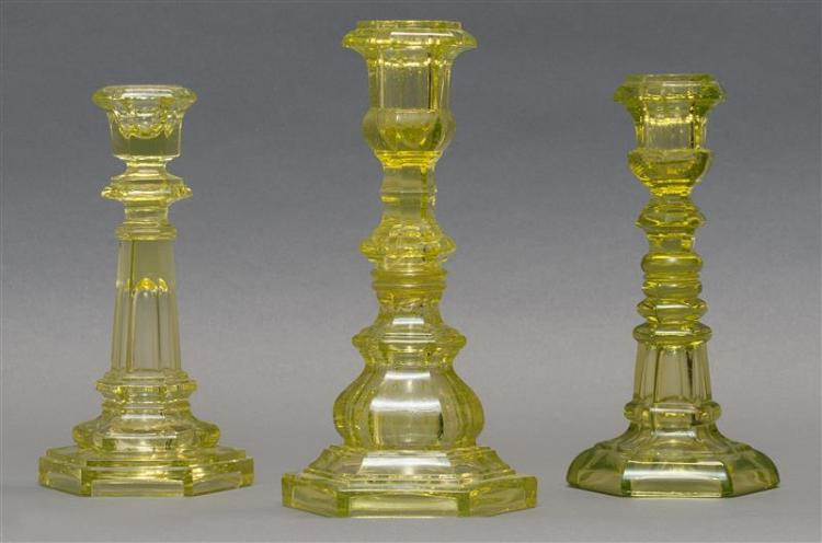 """THREE SANDWICH GLASS COMPANY PRESSED GLASS CANDLESTICKS In varied hexagonal forms. All in canary yellow. Heights from 7.5"""" to 8.5""""...."""