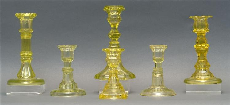 """SIX PRESSED GLASS CANDLESTICKS In varied forms, all in canary yellow. Four by the Sandwich Glass Company. Heights from 4.75"""" to 7.5""""..."""