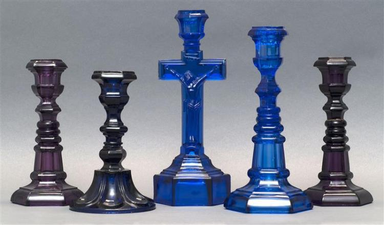 FIVE SANDWICH GLASS COMPANY PRESSED GLASS CANDLESTICKS In varied forms, including one crucifix candlestick. Two in cobalt blue, one...