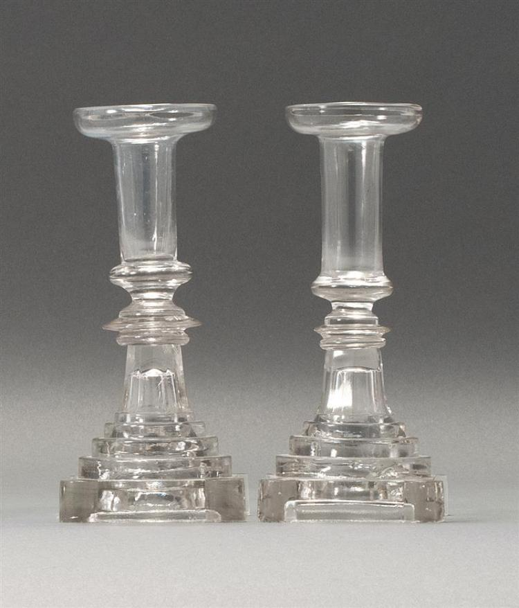 """PAIR OF SANDWICH GLASS COMPANY CLEAR GLASS CANDLESTICKS Free-blown socles and stems on pressed bases. Heights 8.25"""". From a Cape Cod..."""