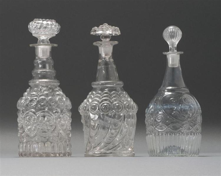 """THREE CLEAR GLASS BLOWN 3-MOLD DECANTERS McKearin #s GV-17, GV-13 and GV-14. All with period stoppers. Heights from 10.5"""" to 11"""". Fr..."""