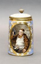 PORCELAIN HALF-LITER LIDDED STEIN Body with painted decoration of a monk holding a glass. Gilt grape and grape leaf design surrounds...