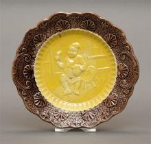CONTINENTAL MAJOLICA PLATE Yellow well with relief decoration of a jolly man in a tavern. Brown lip with scallop shells and scrolls...