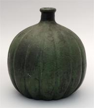 GRUEBY MELON-FORM VASE Bottle neck above a ribbed spherical body. Heavily glazed in matte green with deep, almost black accents. Imp...